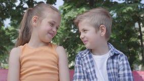 Porträt des netten blonden Jungen und hübschen des Mädchens, die auf dem Schwingen auf dem Spielplatz sitzt Paare von glücklichen stock video footage
