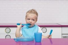 Porträt des netten blonden Kleinkindes in einem blauen Schellfisch mit Gabel und im Messer in seinen Händen im Hochstuhl in der m Stockfotografie