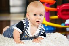 Porträt des netten entzückenden blonden kaukasischen lächelnden Babys mit den blauen Augen, die auf Boden im Kinderkinderraum lie Lizenzfreie Stockfotos
