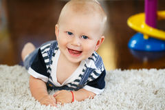 Porträt des netten entzückenden blonden kaukasischen lächelnden Babys mit den blauen Augen, die auf Boden im Kinderkinderraum lie Stockfotografie
