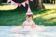 Porträt des netten entzückenden kaukasischen Babys mit dunkelbraunen Augen im rosa Ballettröckchenkleid ihren ersten Geburtstag f Stockfotos