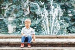 Porträt des netten entzückenden lustigen kaukasischen Kleinkindes des kleinen Jungen im weißen Hemd und in den Blue Jeans Stockbild