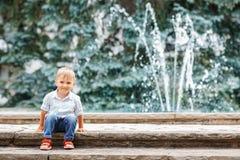 Porträt des netten entzückenden lustigen kaukasischen Kleinkindes des kleinen Jungen im weißen Hemd und in den Blue Jeans Lizenzfreie Stockbilder
