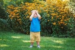 Porträt des netten entzückenden weißen kaukasischen Babykindes, das unter gelben Blumen draußen im Gartenpark steht Lizenzfreie Stockfotos