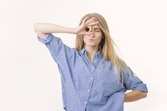 Porträt des netten frohen blonden Mädchens, die Kamera betrachtend durch Finger in der okaygeste lizenzfreie stockfotografie