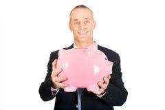 Porträt des netten Geschäftsmannes piggybank halten stockfoto