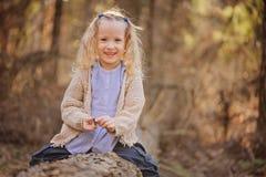 Porträt des netten glücklichen Kindermädchens, das auf dem Baum im Vorfrühlingswald sitzt Stockbild