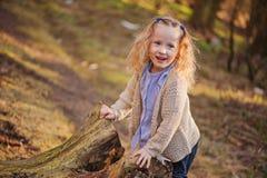 Porträt des netten glücklichen Kindermädchens, das mit Baum im Vorfrühlingswald spielt Stockbild