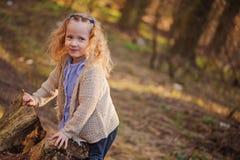 Porträt des netten glücklichen Kindermädchens, das mit Baum im Vorfrühlingswald spielt Stockfotografie