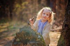 Porträt des netten glücklichen Kindermädchens, das mit Baum im Vorfrühlingswald spielt Lizenzfreies Stockfoto