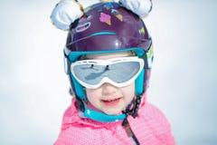 Porträt des netten glücklichen Skifahrermädchens im Sturzhelm und der Schutzbrillen in einem Winterskiort lizenzfreie stockfotografie
