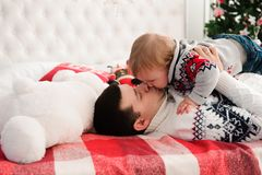 Porträt des netten glücklichen Vaters und des Sohns auf Weihnachten auf Bett lizenzfreie stockfotos