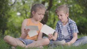 Porträt des netten hübschen Jungen im karierten Hemd und im Mädchen mit dem langen Haar, das Blätter Papier im Park betrachtet stock video