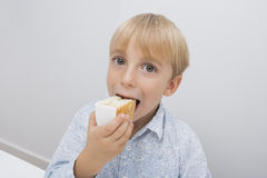 Porträt des netten Jungen Kuchenscheibe im Haus essend Lizenzfreies Stockbild