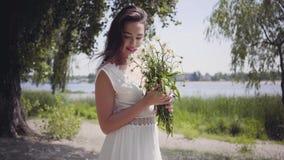 Porträt des netten jungen Mädchens mit dem langen brunette Haar, das eine lange weiße Sommermode-Kleiderstellung im Park trägt stock video