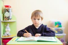 Porträt des netten Jungen mit Skizzenstift und des Buches am Schreibtisch im Klassenzimmer stockbilder