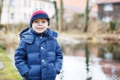 Porträt des netten kaukasischen Kleinkindjungen in der warmen Kleidung auf kaltem d Stockfotografie