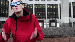 Porträt des netten Kerls in der Jacke und in Sonnenbrille, die nahe bei Granitsäulen klopfen stock footage
