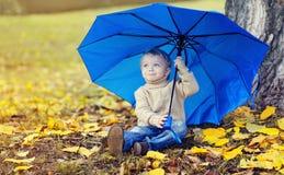 Porträt des netten Kindes mit dem Regenschirm, der auf gelben Blättern sitzt Stockbilder