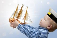 Kleiner Kapitän mit dem Schiff Stockfotografie