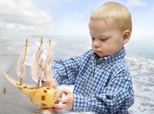 Kleiner Kapitän mit dem Schiff Stockfoto
