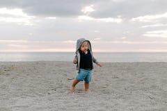 Porträt des netten kleinen Baby-Kindes, das draußen im Sand am Strand während des Sonnenuntergangs im Urlaub im Hoodie spielt und stockfotos