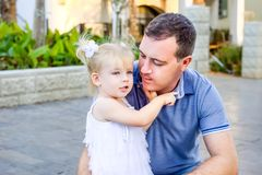 Porträt des netten kleinen blondy Kleinkindmädchens im weißen Kleid, das ihren Vater umarmt und ihm etwas während des Wegs im Sta lizenzfreie stockbilder