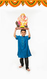 Porträt des netten kleinen indischen Jungen, der ein Ganesh-Idol oder Lord ganesha oder ganapati murti /statue über seinem Kopf,  Stockbilder