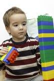 Porträt des netten kleinen Jungen, der Tuch mit lego macht Stockfotos