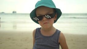 Porträt des netten kleinen Jungen im Strohhut mit der Sonnenbrille, die auf Sommerstrand steht stock video