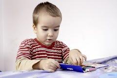 Porträt des netten kleinen Jungen mit Markierungen im Bett Stockbilder