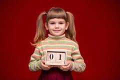 Porträt des netten kleinen Mädchens, das auf hölzernem Kalender des roten Griffs lokalisiert wurde, stellte an September erster e lizenzfreie stockfotografie