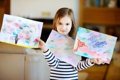 Porträt des netten kleinen Mädchens, das ihre Zeichnungen zeigt Lizenzfreie Stockfotografie