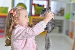 Porträt des netten kleinen Mädchens, das mit Chinchilla spielt stockbild