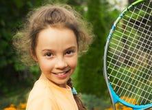 Porträt des netten kleinen Mädchens, das Tennis im Sommer spielt Stockfoto