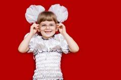 Porträt des netten kleinen Mädchens in den sehr großen Gläsern lokalisiert auf Rot Konzept des Sehvermögens oder des Unterrichten lizenzfreie stockfotografie