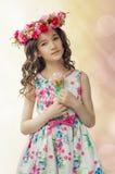Porträt des netten kleinen Mädchens im netten Frühlingskleid, mit Blumenkranz auf Kopf, hält rosa stieg in Hände Lizenzfreie Stockfotos