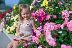 Porträt des netten kleinen Mädchens nahe den Blumen herein Stockbild