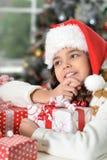 Porträt des netten kleinen Mädchens in Sankt-Hut mit Geschenken für Weihnachten lizenzfreies stockbild