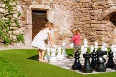 Porträt des netten kleinen Mädchens und des Jungen, die Schach spielt Lizenzfreie Stockfotos