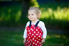 Porträt des netten Kleinkindmädchens, das draußen schönes Baby in der Hose des roten Gummis hat Spaß am sonnigen warmen Sommertag Lizenzfreie Stockfotos