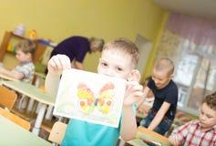 Porträt des netten lächelnden Jungen, der ein helles buntes Bild des Schmetterlinges hält, malte Farben und Zeichenstifte im Kind Stockfoto