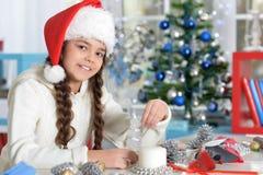 Porträt des netten lächelnden kleinen Mädchens, das für Weihnachten sich vorbereitet lizenzfreie stockbilder