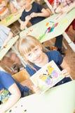Porträt des netten lächelnden Mädchens, das ein helles buntes Bild des Schmetterlinges hält, malte Farben und Zeichenstifte im Ki Stockfoto
