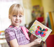 Porträt des netten lächelnden Mädchens, das ein helles buntes Bild des Schmetterlinges hält, malte Farben und Zeichenstifte im Ki Stockbild