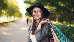 Porträt des netten Mädchenkäufers, der mit Papiertüten, die Kamera-, Lächeln und Lachenstellung in der Straße betrachtend aufwirf stock footage