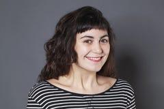 Porträt des netten Mädchens des Brunette 20s mit natürlichem Lächeln Lizenzfreie Stockfotografie
