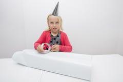Porträt des netten Mädchens Geburtstagsgeschenk im Haus bei Tisch einwickelnd Lizenzfreies Stockbild