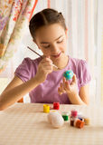 Porträt des netten Mädchens mit der Bürste, die Ostereier malt Stockbild