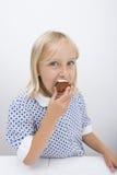 Porträt des netten Mädchens Muffin im Haus bei Tisch essend Lizenzfreie Stockfotos